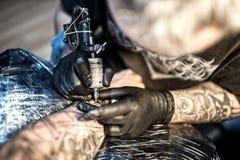 Καλλιτέχνης στο σχέδιο καταστημάτων δερματοστιξιών με το μελάνι στο δέρμα Στοκ Φωτογραφία