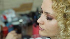 Καλλιτέχνης Makeup που δημιουργεί το όμορφο makeup για το ξανθό κορίτσι Μάτια Smokey για το πρότυπο μόδας απόθεμα βίντεο