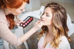 Καλλιτέχνης Makeup που προετοιμάζει τη νύφη πριν από το γάμο ένα πρωί στοκ φωτογραφία