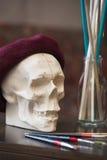 Καλλιτεχνική ατμόσφαιρα: βάζο με το χρωματισμένο νερό, κρανίο beret Δημιουργική διάθεση Στοκ Εικόνα