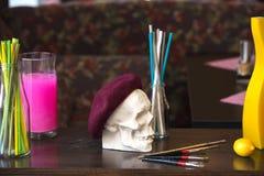 Καλλιτεχνική ατμόσφαιρα: βάζο με το χρωματισμένο νερό, κρανίο beret Δημιουργική διάθεση Στοκ Εικόνες