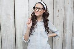 Καλλιτεχνική καθιερώνουσα τη μόδα γυναίκα με τα μοντέρνα γυαλιά που θέτουν το πινέλο εκμετάλλευσης Στοκ Φωτογραφία