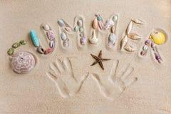 Καλοκαίρι λέξης που γράφεται κοντά στην άμμο, με το υπόβαθρο τυπωμένων υλών χεριών Στοκ Φωτογραφία