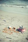 Καλοκαίρι 2017 επιγραφής, εξαρτήματα για την ηλιοθεραπεία και διαβατήριο με το δολάριο νομισμάτων στην άμμο στην παραλία, θερινός Στοκ Εικόνες