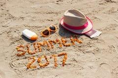 Καλοκαίρι 2017 επιγραφής, εξαρτήματα για την ηλιοθεραπεία και διαβατήριο με το δολάριο νομισμάτων στην άμμο στην παραλία, θερινός Στοκ Εικόνα