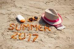 Καλοκαίρι 2017 επιγραφής, εξαρτήματα για την ηλιοθεραπεία και διαβατήριο με το δολάριο νομισμάτων στην άμμο στην παραλία, θερινός Στοκ Φωτογραφία