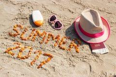 Καλοκαίρι 2017 επιγραφής, εξαρτήματα για την ηλιοθεραπεία και διαβατήριο με το δολάριο νομισμάτων στην παραλία, έννοια θερινού χρ Στοκ Φωτογραφία