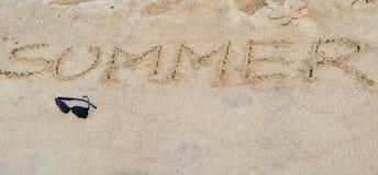 Καλοκαίρι και γυαλιά ηλίου λέξης στην άμμο παραλιών Στοκ εικόνες με δικαίωμα ελεύθερης χρήσης