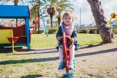 Καλοκαίρι, παιδική ηλικία, ελεύθερος χρόνος και έννοια ανθρώπων - ευτυχές μικρό κορίτσι στην παιδική χαρά παιδιών Στοκ εικόνα με δικαίωμα ελεύθερης χρήσης
