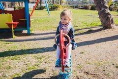 Καλοκαίρι, παιδική ηλικία, ελεύθερος χρόνος και έννοια ανθρώπων - ευτυχές μικρό κορίτσι στην παιδική χαρά παιδιών Στοκ φωτογραφία με δικαίωμα ελεύθερης χρήσης
