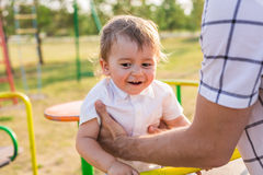 Καλοκαίρι, παιδική ηλικία, ελεύθερος χρόνος και έννοια παιδιών - ευτυχές αγόρι στην παιδική χαρά παιδιών με τον πατέρα του Στοκ Εικόνες