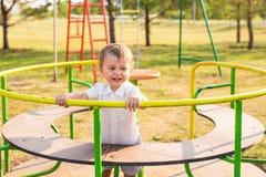 Καλοκαίρι, παιδική ηλικία, ελεύθερος χρόνος και έννοια παιδιών - ευτυχές αγόρι στην παιδική χαρά παιδιών Στοκ Εικόνες