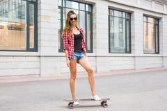Καλοκαιρινές διακοπές, ακραίος αθλητισμός και έννοια ανθρώπων - ευτυχές κορίτσι που οδηγά σύγχρονο skateboard στην οδό πόλεων Στοκ Φωτογραφία