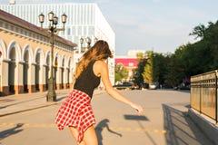 Καλοκαιρινές διακοπές, ακραίος αθλητισμός και έννοια ανθρώπων - ευτυχές οδηγώντας skateboard κοριτσιών στην οδό πόλεων Στοκ Εικόνες