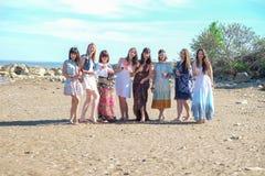 Καλοκαιρινές διακοπές και έννοια διακοπών - χαμογελώντας νέων γυναικών με τα ποτά στην παραλία στοκ φωτογραφία