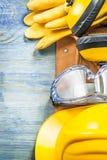 Καλυμμάτων αυτιών η προστατευτική γυαλιών ζώνη οικοδόμησης καπέλων γαντιών σκληρή επιζητά επάνω Στοκ Φωτογραφία