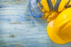 Καλυμμάτων αυτιών προστατευτικά προστατευτικά δίοπτρα καπέλων γαντιών σκληρά στα ξύλινα μειονεκτήματα πινάκων Στοκ φωτογραφία με δικαίωμα ελεύθερης χρήσης