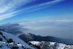Καλυμμένα βουνά σύννεφα και χιόνι στοκ εικόνα
