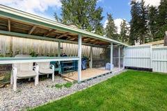 Καλυμμένη περιοχή patio με τις εξωτερικές καρέκλες στον κήπο κατωφλιών Στοκ Εικόνες