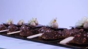 καλυμμένος σοκολάτα πάγ& Παγωτό σοκολάτας σε ένα ραβδί Παγωτό σοκολάτας σε ένα ραβδί που διακοσμείται με τα λουλούδια απόθεμα βίντεο