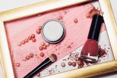 Καλλυντικά Οι διεσπαρμένες σκιές, applicator, σφαίρες κοκκινίζουν και καρφώνουν τη στιλβωτική ουσία σε ένα χρυσό πλαίσιο αφαίρεση Στοκ φωτογραφία με δικαίωμα ελεύθερης χρήσης