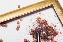 Καλλυντικά Οι διεσπαρμένες σκιές, applicator, σφαίρες κοκκινίζουν σε ένα χρυσό πλαίσιο αφαίρεση Στοκ εικόνα με δικαίωμα ελεύθερης χρήσης