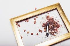 Καλλυντικά Οι διεσπαρμένες σκιές, applicator, σφαίρες κοκκινίζουν σε ένα χρυσό πλαίσιο αφαίρεση Στοκ φωτογραφία με δικαίωμα ελεύθερης χρήσης