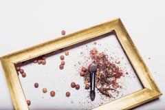 Καλλυντικά Οι διεσπαρμένες σκιές, applicator, σφαίρες κοκκινίζουν σε ένα χρυσό πλαίσιο αφαίρεση Στοκ Φωτογραφίες