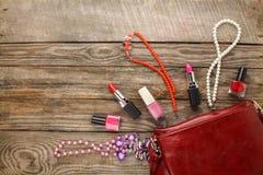Καλλυντική τσάντα εξαρτημάτων γυναικών ` s, περιδέραιο, στιλβωτική ουσία καρφιών, κραγιόν Στοκ Φωτογραφία