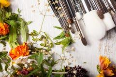 Καλλυντικός αποτελέστε τις βούρτσες δίπλα στα άγρια λουλούδια Στοκ Εικόνες