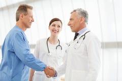 Καλωσορίστε εν πλω! Χειραψία δύο ώριμη γιατρών ενώ beautifu Στοκ εικόνες με δικαίωμα ελεύθερης χρήσης