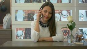 Καλός σύμβουλος πωλητών που έχει ένα τηλεφώνημα και ένα χαριτωμένο χαμόγελο σε ένα κατάστημα κοσμήματος φιλμ μικρού μήκους