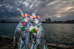 Καλό έγχρωμο ζεύγος στο ηλιοβασίλεμα κατά τη διάρκεια της Βενετίας καρναβάλι Στοκ Εικόνες