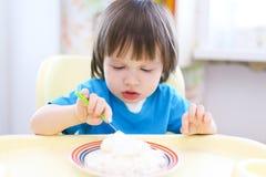 Καλό αγόρι μικρών παιδιών που τρώει το θεωρητικό και υποατομικό σωματίδιο με την ξινή κρέμα Στοκ Φωτογραφίες