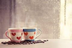 Καλό γυαλί δύο με το φασόλι καφέ στο βροχερό παράθυρο ημέρας Στοκ Εικόνες