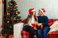Καλό ευτυχές ζεύγος στον καναπέ με τα δώρα Χριστουγέννων Στοκ Φωτογραφία