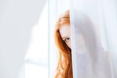 Καλό κρύψιμο γυναικών πίσω από τις άσπρες κουρτίνες στοκ φωτογραφία με δικαίωμα ελεύθερης χρήσης