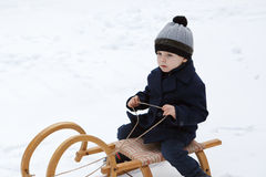 Καλό μικρό παιδί στο αρχαίο έλκηθρο τη χειμερινή ημέρα Στοκ Εικόνα