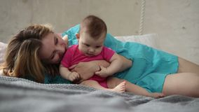 Καλό παιχνίδι μητέρων με το νεογέννητο παιδί στο κρεβάτι απόθεμα βίντεο