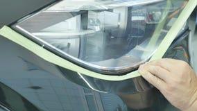 Καλύπτοντας μέρη αυτοκινήτων ζωγράφων σώματος με κάποια ταινία και έγγραφο απόθεμα βίντεο