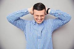 καλύπτοντας τα αυτιά το άτομό του Στοκ εικόνα με δικαίωμα ελεύθερης χρήσης