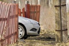 Καλύπτρα αυτοκινήτων πίσω από έναν παλαιό φράκτη στις αγροτικές περιοχές στοκ φωτογραφία