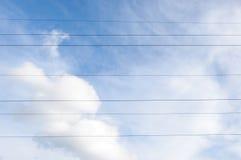 Καλώδια γραμμών ηλεκτρικής ενέργειας ενάντια στον μπλε νεφελώδη ουρανό Στοκ Φωτογραφίες