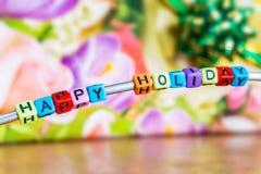Κείμενο από το ντεκόρ, ευτυχείς διακοπές, σε ένα floral υπόβαθρο στοκ εικόνες με δικαίωμα ελεύθερης χρήσης