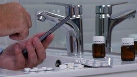 Κείμενο ατόμων που χρησιμοποιεί το κινητό τηλέφωνο στο λουτρό με τα χάπια και τα φάρμακα στο νεροχύτη απόθεμα βίντεο