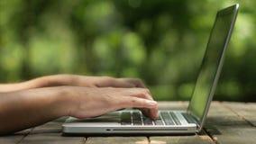 Κείμενο δακτυλογράφησης ατόμων στο lap-top στον κήπο απόθεμα βίντεο