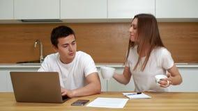 Κείμενο δακτυλογράφησης νεαρών άνδρων στο φορητό προσωπικό υπολογιστή Το κορίτσι φέρνει το φλιτζάνι του καφέ στο φίλο φιλμ μικρού μήκους