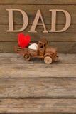 Κείμενο μπαμπάδων από τη μορφή καρδιών στο φορτηγό παιχνιδιών στον ξύλινο πίνακα Στοκ Φωτογραφία