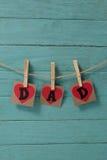 Κείμενο μπαμπάδων στις μορφές καρδιών που κρεμά στον πράσινο τοίχο Στοκ Εικόνες