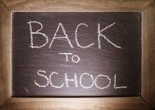 Κείμενο πίσω στη σχολική έννοια που γράφεται στον πίνακα κιμωλίας με το ξύλινο πλαίσιο Στοκ Εικόνες
